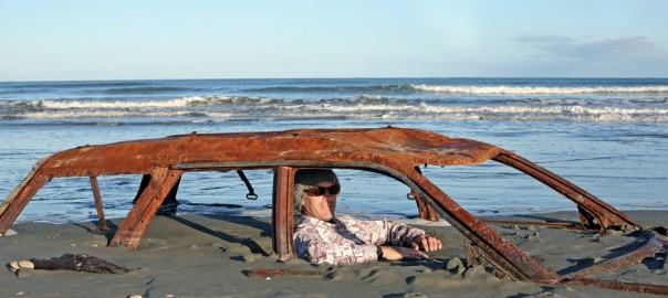 Rusty car buried on beach